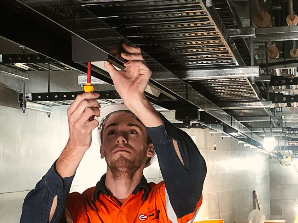 Electrician installing overhead cable trays in commercial construction site in Tasmania